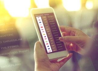 Hand som håller i en iPhone for å sjekke ut valutakurser.