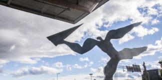 Statue av mann som kaster et papirfly på Gardermoen flyplass i Norge.